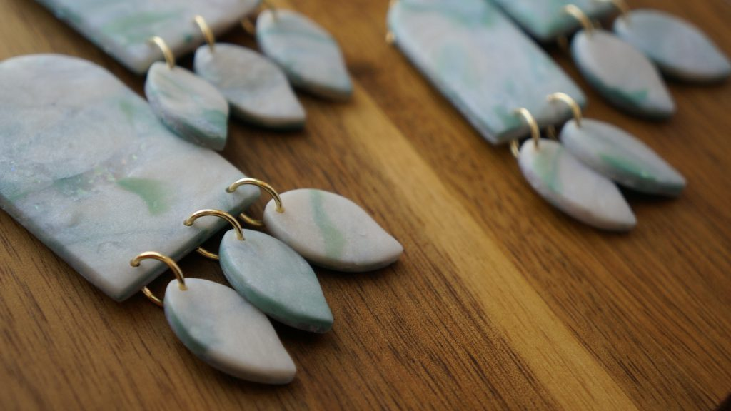 A pair of dangle earrings are laid flat on a finished piece of wood. They have an arch shape as the base and three smaller leaf-life shapes hanging down. The earrings are a mix of pearly white and sage-blue and have gold components.