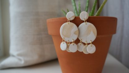 A pair of dangle earrings hang from the edge of a terracotta pot that holds an aloe vera plant. They have a circle core. Three smaller circles hang down from the circle. The color is a modgepodge of a pearly cream and tan-tinted translucent.