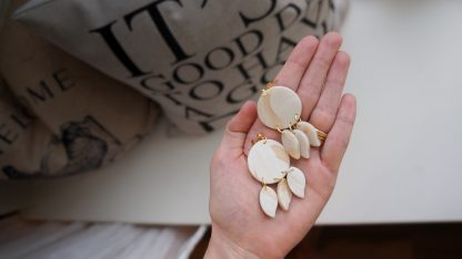 A pair of dangle earrings are laid out flat on an open hand. They have a circle core. Three leaf-like shapes hang down from the circle. The color is a modgepodge of a pearly cream and tan-tinted translucent.