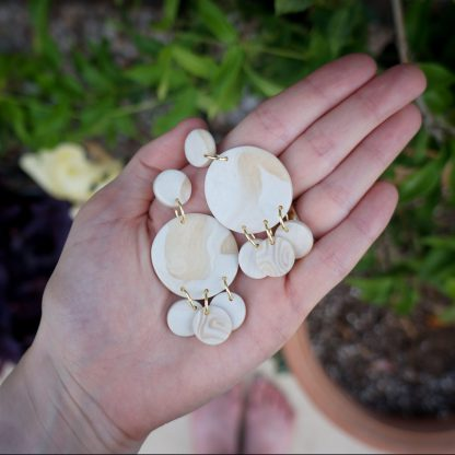 A pair of dangle earrings are laid flat in an open hand. They have a circle core. Three smaller circles hang down from the circle. The color is a modgepodge of a pearly cream and tan-tinted translucent.